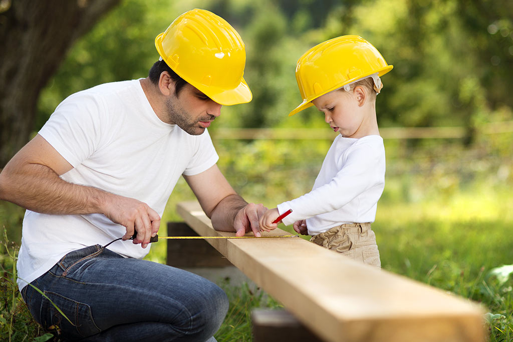 A boy and his father working together.