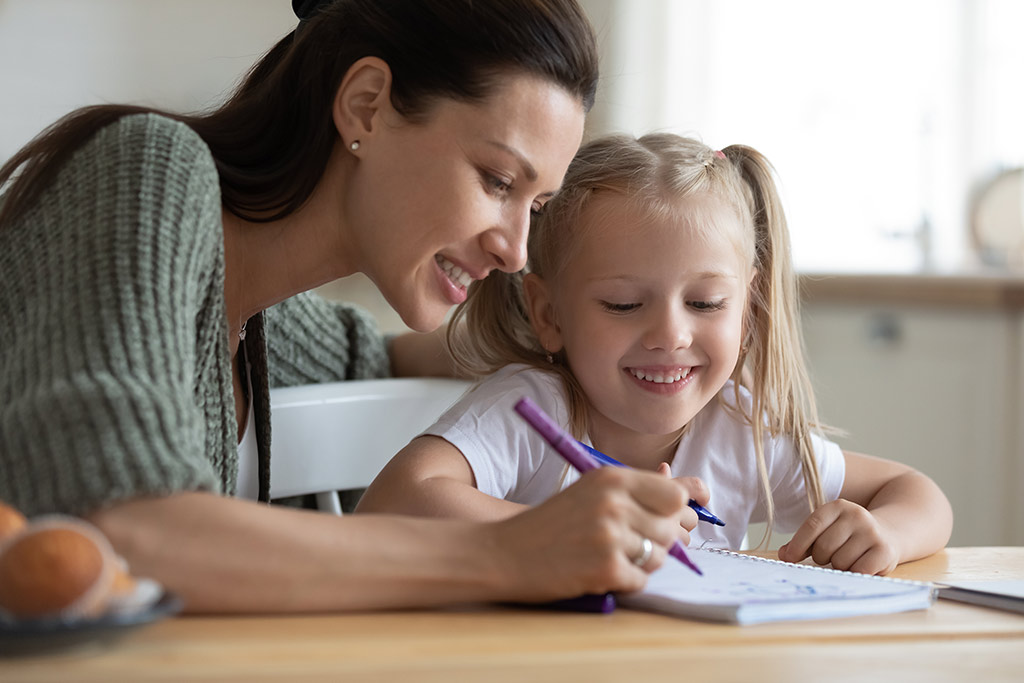 A mother helpinh her daughter how to write.