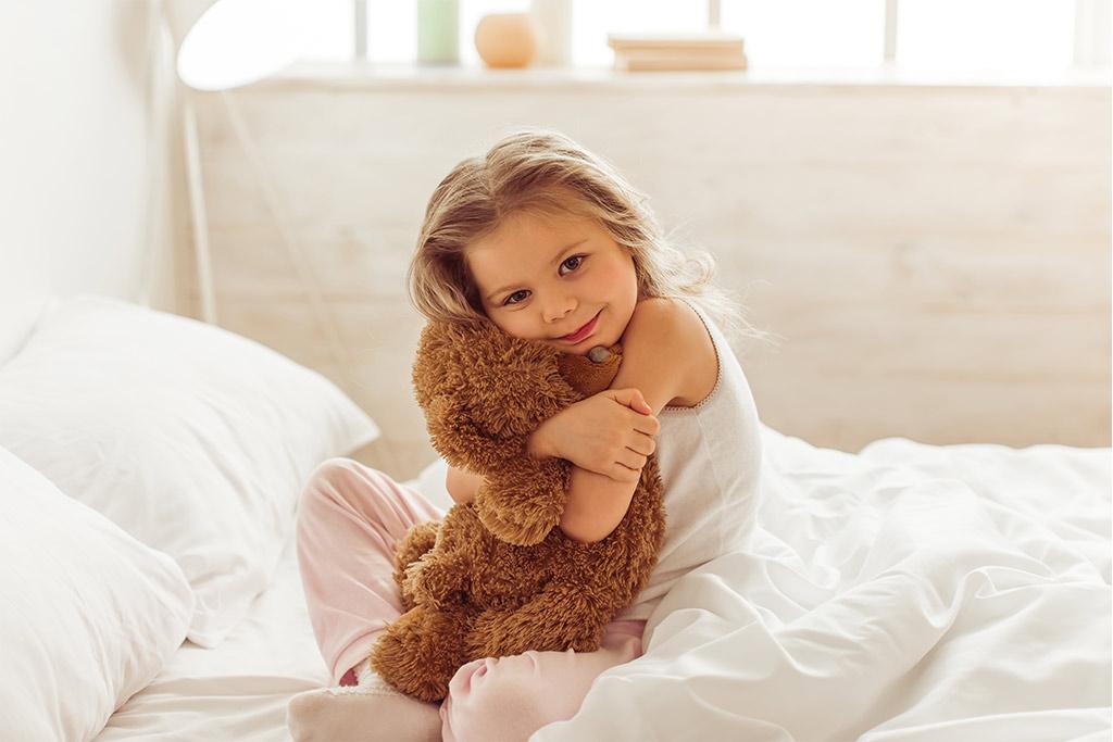 A child hugging a Teddy Bear
