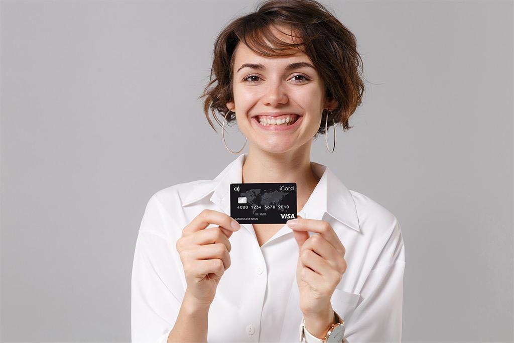 A girl holding iCard Visa Infinite card.